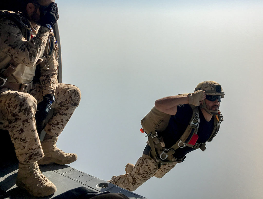 Bahrain Defense Forces paratrooper salutes as he jumps
