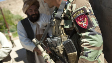 An Afghan National Army special forces soldier, right, talks with a potential Afghan Local Police candidate in Helmand province, Afghanistan
