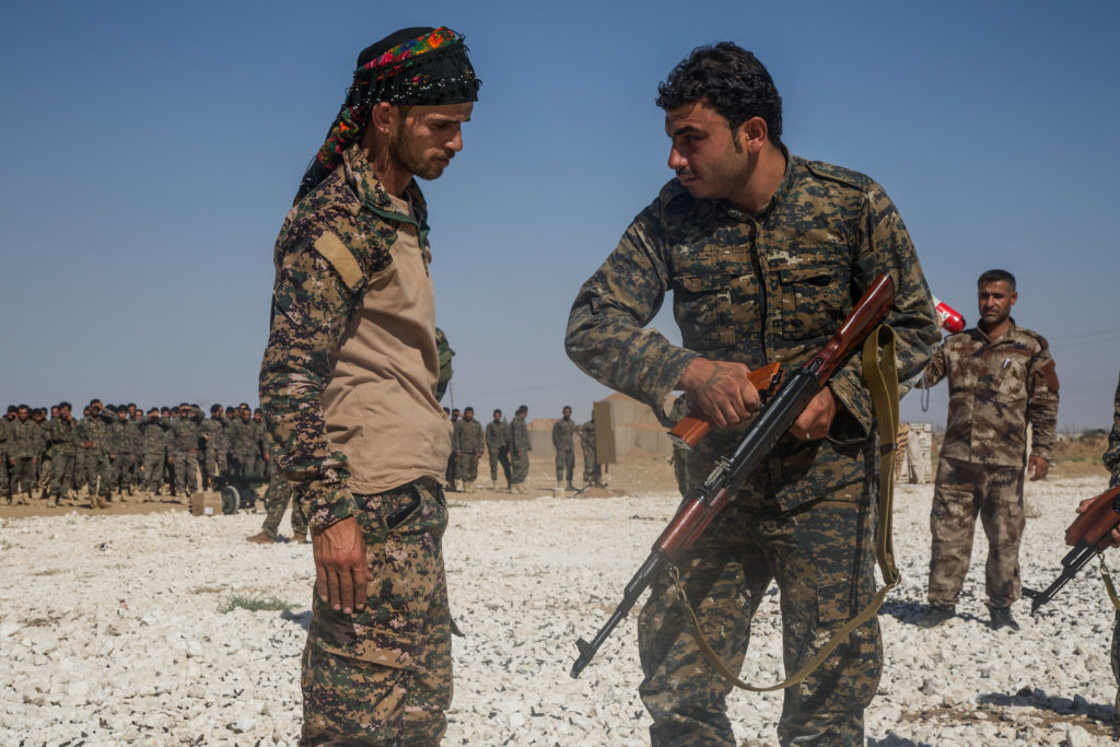 An instructor with the Syrian Democratic Forces observes a Syrian Arab trainee clear his rifle during small arms training in Northern Syria,