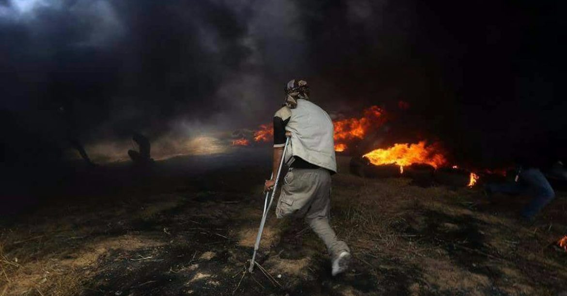 A Palestinian man in Gaza approaches a tire fire