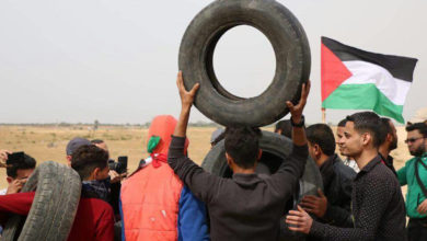 A group of young men in Gaza prepare to light tires on fire ahead of a protest
