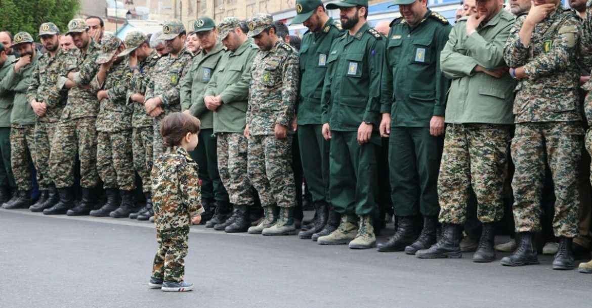 Islamic Revolutionary Guard Corps officers in tears as they look at the son of one of their colleagues, Akbar Zavar Jannati, who was killed in an airstrike in Syria