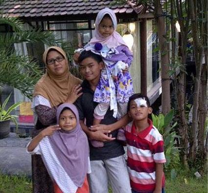 Puji Kuswati poses with her four children