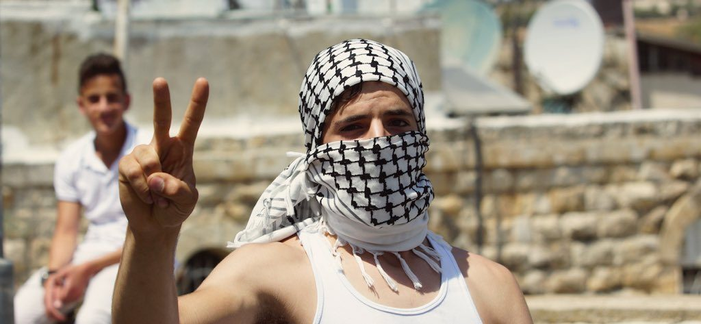 A Palestinian rock thrower poses as clashes break out over al-Aqsa mosque in east Jerusalem