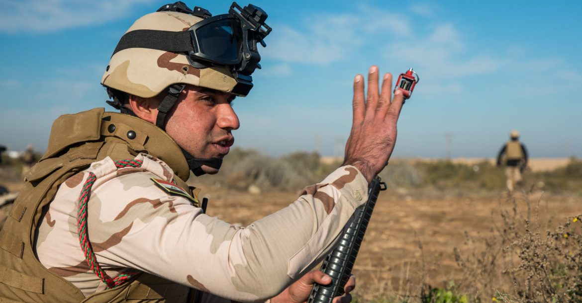 Iraqi Army soldier signals for others to move forward