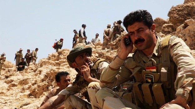 A Peshmerga forces member provides a report to his commander during a joint clearance operation in the Makhmour Mountains region, Iraq