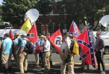 "Alt-right members preparing to enter Emancipation Park holding Nazi, Confederate Battle, Gadsden ""Don't Tread on Me,"" Southern Nationalist, and Thor's Hammer flags."