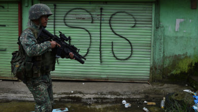 A Philippine Marine walks past graffiti during a patrol along a deserted street at the frontline in Marawi, on the southern island of Mindanao on July 22, 2017.