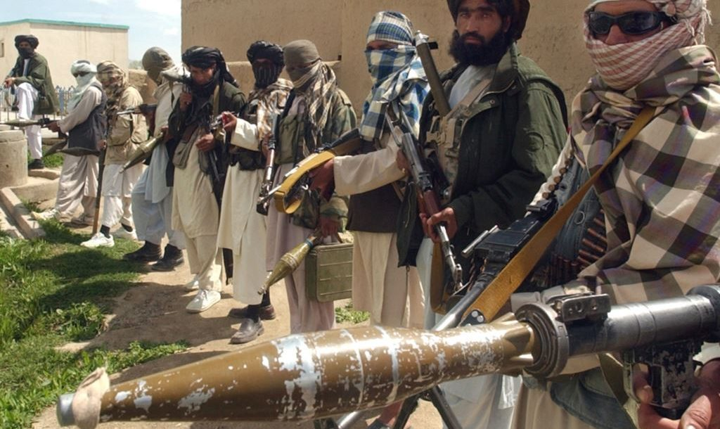 Taliban militants in a line holding guns and explosives