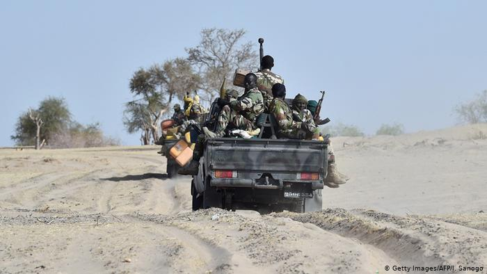 Nigerian soldiers traveling on the back of a pick-up truck.