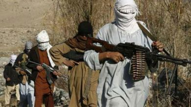 Taliban fighters patrol an area in rural Afghanistan