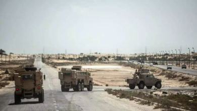 Egyptian officers drive on a route leading to El-Arish, the capital of North Sinai province, Egypt, on July 26, 2018.