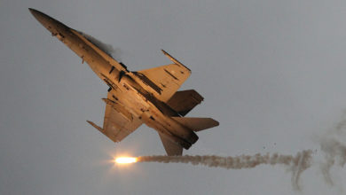 "A McDonnell Douglas F-18 Hornet military airplane of the Finnish Air Force emits so-called ""flares"" countermeasure munition during the International Air Show ILA in Schoenefeld near Berlin on September 15, 2012"