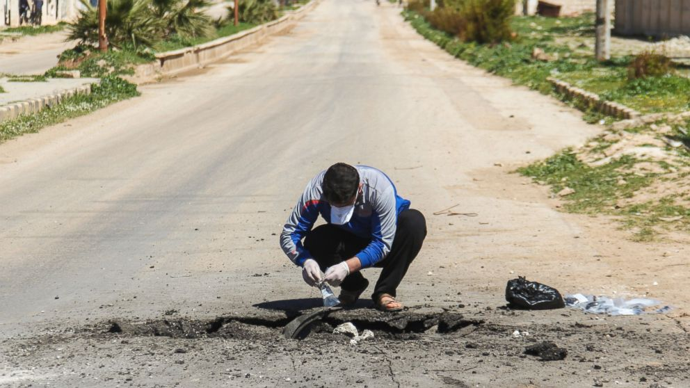 A Syrian man collects samples from the site of a suspected toxic gas attack in Syria's Idlib province, April 5, 2017