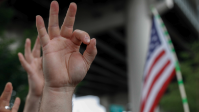 A demonstrator makes a hand gesture believed to have white supremacist connotations, Aug. 17, 2019, in Portland, Oregon, United States