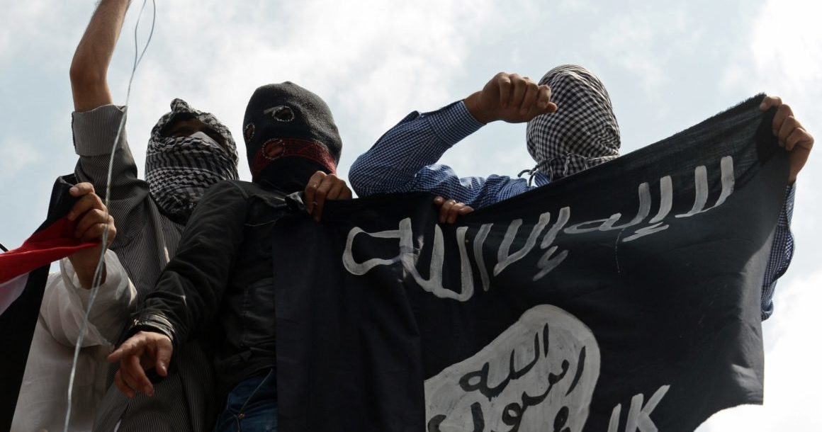 Islamic State supporters hold up the caliphate's flag