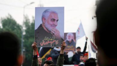 Mourners hold up pictures of General Qassem Soleimani at his funeral in January 2020.