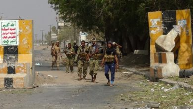 Armed Yemeni soldiers walk on.