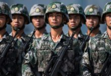Chinese soldiers look on.