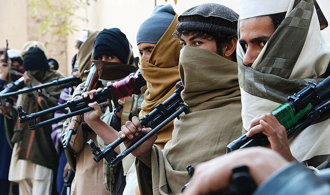 Taliban fighters holding weapons stand in a queue