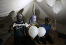 "asked Palestinians calling themselves the ""night confusion units"" hold incendiary devices attached to balloons to be flown into Israel, near the Gaza-Israel border east of Rafah, September 2018."