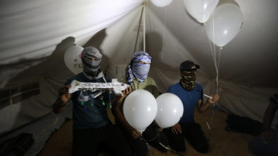 """asked Palestinians calling themselves the """"night confusion units"""" hold incendiary devices attached to balloons to be flown into Israel, near the Gaza-Israel border east of Rafah, September 2018."""