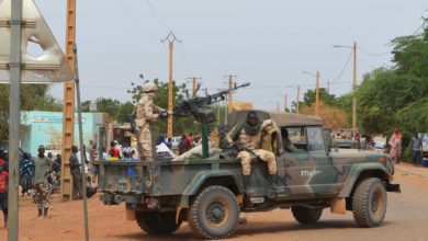 Malian soldiers ride on a pick up truck with a machine gun on November 13, 2018, in Gao