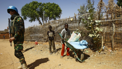 Sudanese boys push a wheelbarrow past a United Nations peace keeper at the El-Riyadh camp for internally displaced persons in el-Geneina, on February 8, 2017