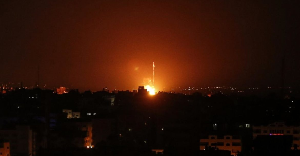 Flames are seen at a distance after Israel carried out airstrikes over Gaza.