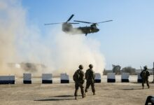 American troops walk as a US Army C-47 Chinook helicopter flies over the village of Oreij, south of Mosul, Iraq