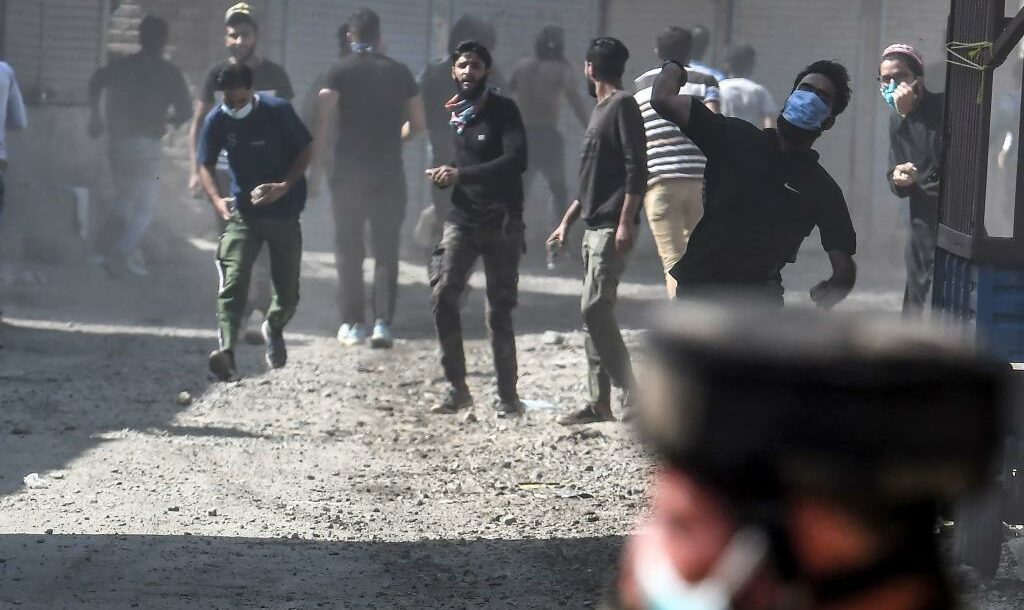 Protesters throw stones during clashes with government forces in Batamaloo area of Srinagar on September 17, 2020