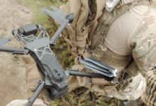A man in defense outfit holding a Skydio X2 drone.