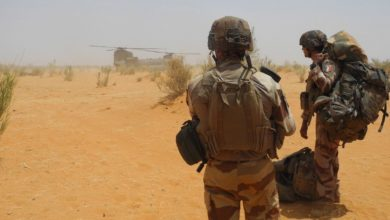 Two French soldiers wait to board a helicopter in east-central Mali.