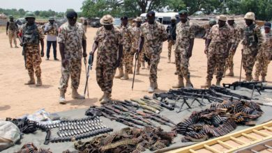 Military troops inspect arms and ammunitions recovered from Boko Haram jihadists.