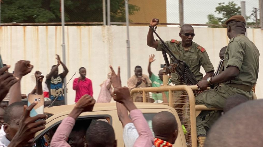 Malian soldiers surrounded by villagers.