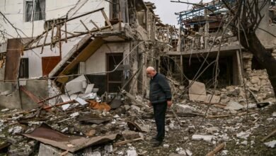 An elderly man stands in front of a destroyed house after shelling in the occupied Nagorno-Karabakh region's main city of Stepanakert.