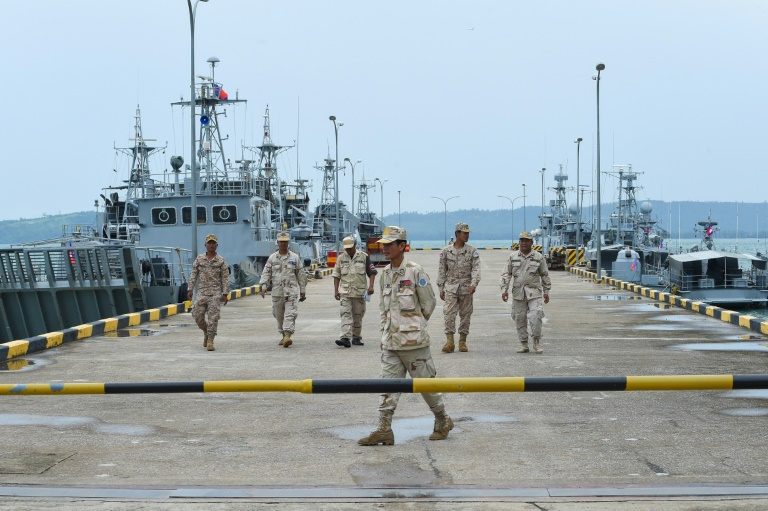 Cambodian navy personnel walk on a jetty at the Ream naval base during a government-organised media tour in July, 2019