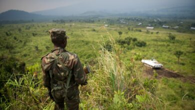 A soldier from the Armed Forces of the Democratic Republic of the Congo (FARDC) stands guard on a hill overlooking a United Nations tank position near the village of Kibumba I, around 20km from the city of Goma in the Democratic Republic of the Congo's restive North Kivu province on July 11, 2012.