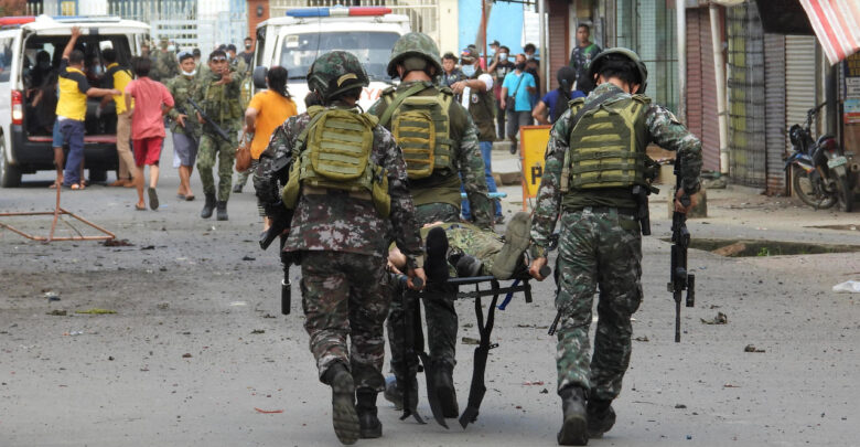 Military personnel carry an injured victim after the twin bombing in Philippines.
