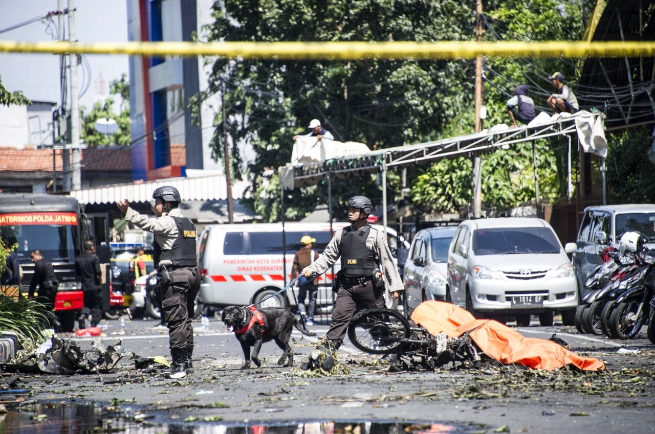 K9 police examine a site following attacks outside the Surabaya Centre Pentecostal Church.