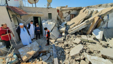 Civilians examining a damaged building.