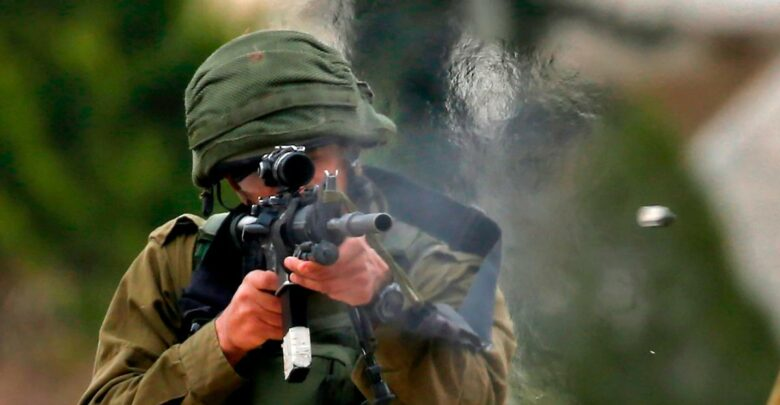An Israeli soldier fires rubber bullets at Palestinian protesters during a weekly demonstration against the expropriation of Palestinian lands in the occupied West Bank, on February 1, 2019