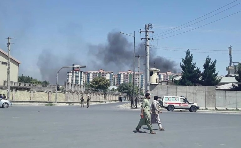 Afghan men walk on a road as smoke rises from the site of an attack in Kabul on 1 July 2019.