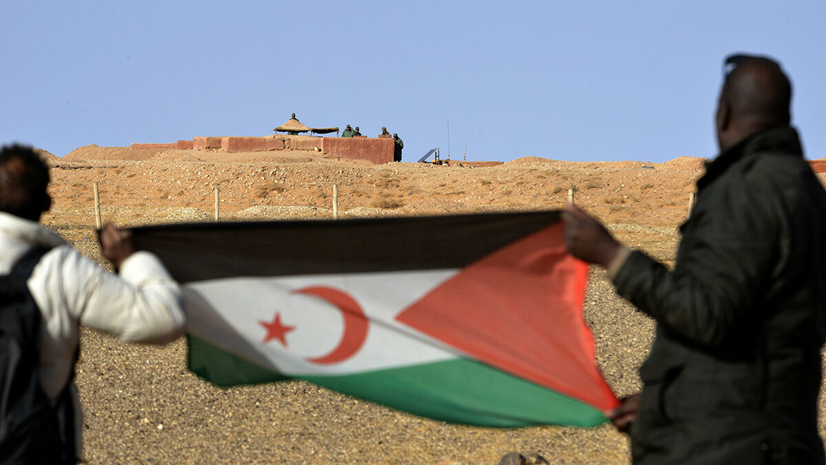 Saharawi men hold up a Polisario Front flag in the Al-Mahbes area near Moroccan soldiers guarding the wall separating the Polisario controlled Western Sahara from Morocco on February 3, 2017.