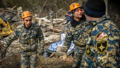 Rescuers carry the body of a woman killed by shelling during the military conflict over the Nagorno-Karabakh region.