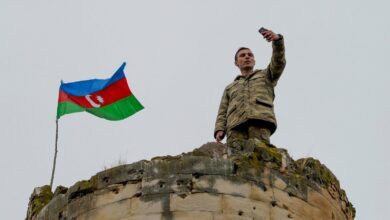 An Azerbaijani soldier takes a selfie with the national flag in Fuzuli, a liberated city, last November 26, 2020.