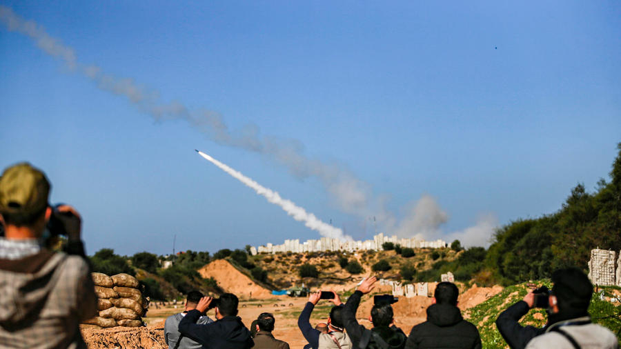 People watch as rockets are fired into the sea during a military drill in Gaza to mark the anniversary of the start of the 2008 conflict with Israel