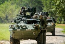 A column of eight-wheeled Stryker combat vehicles moves along a road at Fort Benning, Georgia, September 2, 2020 during training