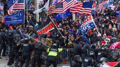 Police and security forces attempt to hold back a mob of pro-Trump extremists as they storm the US Capitol in Washington on January 6, 2021.