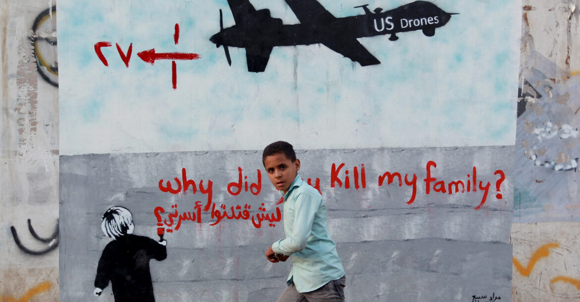 "A Yemeni boy walks past a mural depicting a US drone and reading ""Why did you kill my family"" on December 13, 2013 in the capital Sana"